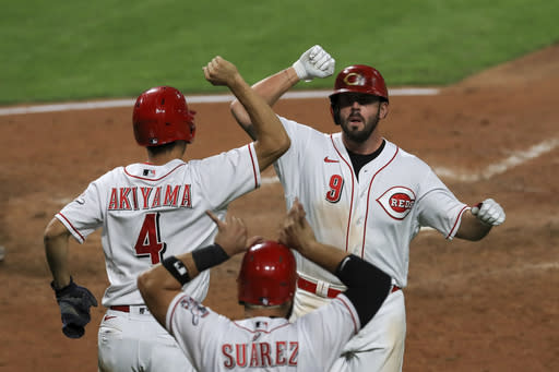 Cincinnati Reds' Shogo Akiyama, left, celebrates a three-run home run by Mike Moustakas, right, in the fifth inning during a baseball game against the Pittsburgh Pirates in Cincinnati, Monday, Sept. 14, 2020. (AP Photo/Aaron Doster)