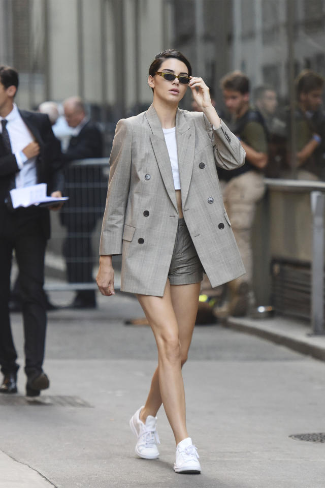 <p>In an over-sized blazer, high-waisted shorts, a white crop top and Adidas Stan Smith sneakers while out in Paris. </p>