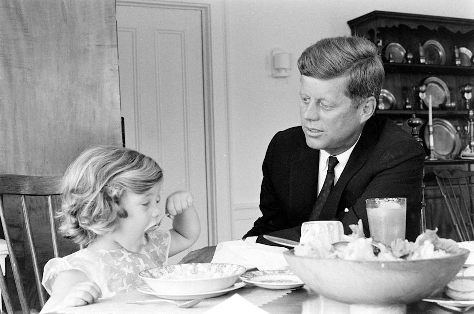 <p>Senator John F. Kennedy sitting with Caroline as he goes over some papers at the kitchen table in his Georgetown home. He had recently been nominated as the presidential candidate for the Democratic Party.</p>