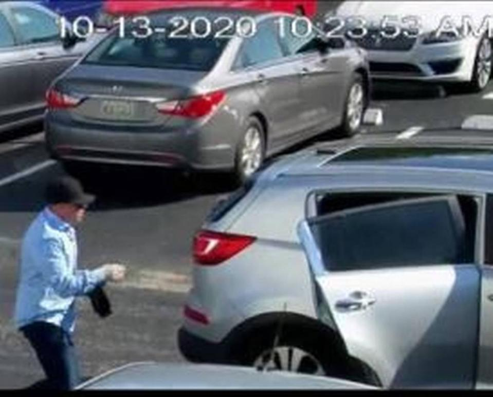 One of the would-be armed robbers jumps in the Kia Sportage to leave the Castle Apartments' parking lot.