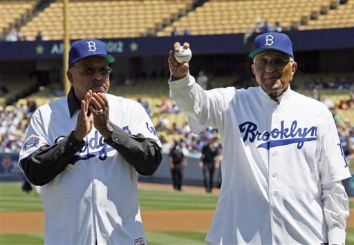 Dodger greats Tommy Davis, left, and Don Newcombe are honored before both threw out ceremonial pitches in a baseball game between the Los Angeles Dodgers and the San Diego Padres in Los Angeles Sunday, April 15, 2012. (AP Photo/Reed Saxon)