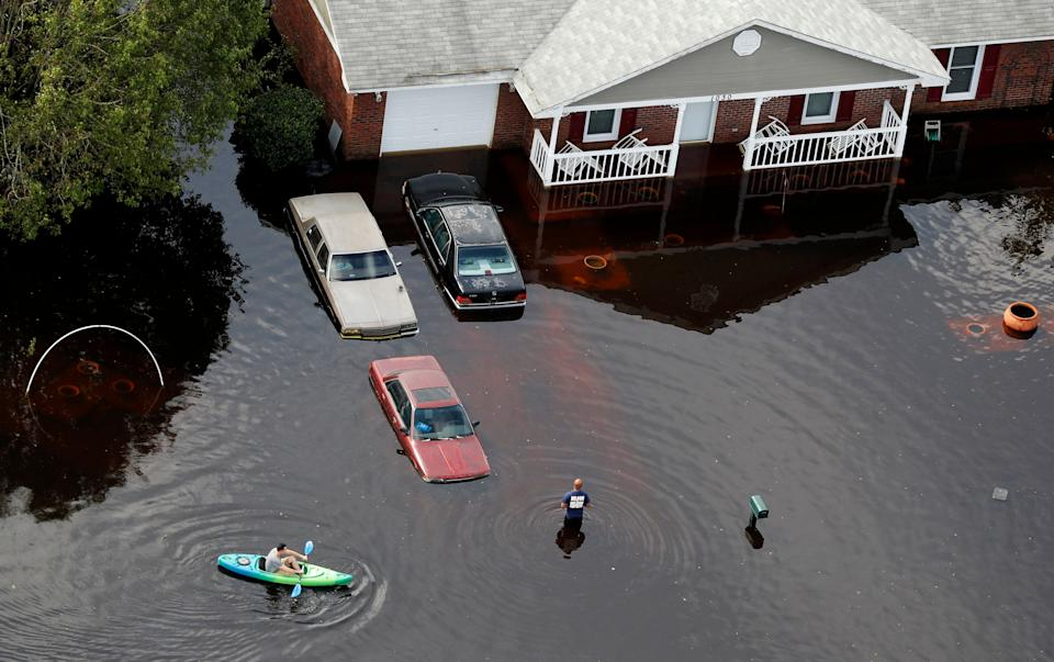 A man paddles a kayak in a neighborhood in Fayetteville, North Carolina.