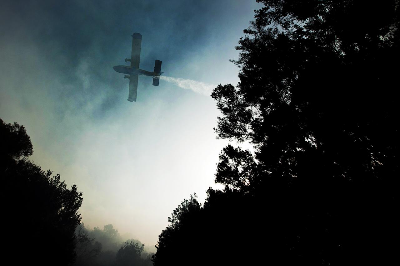 A plane works to extinguish a wildfire in La Gomera, Spain, Sunday, Aug. 12, 2012. Wildfires spurred by high temperatures raged across Spain's Canary Islands of La Gomera and Tenerife as well as Ourense in northwestern Spain. Flames are threatening some of Europe's oldest surviving forests in the Garajonay National Park in La Gomera and have forced the evacuation of hundreds of people across the country. (AP Photo/Andres Gutierrez)