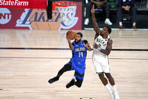 Orlando Magic's D.J. Augustin (14) goes up for a shot as Milwaukee Bucks' Eric Bledsoe (6) defends during the first half of an NBA basketball first round playoff game Saturday, Aug. 29, 2020, in Lake Buena Vista, Fla. (AP Photo/Ashley Landis)