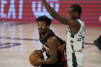 Miami Heat's Jimmy Butler, left, drives against Milwaukee Bucks' Khris Middleton (22) in the first half of an NBA conference semifinal playoff basketball game Tuesday, Sept. 8, 2020 in Lake Buena Vista, Fla. (AP Photo/Mark J. Terrill)
