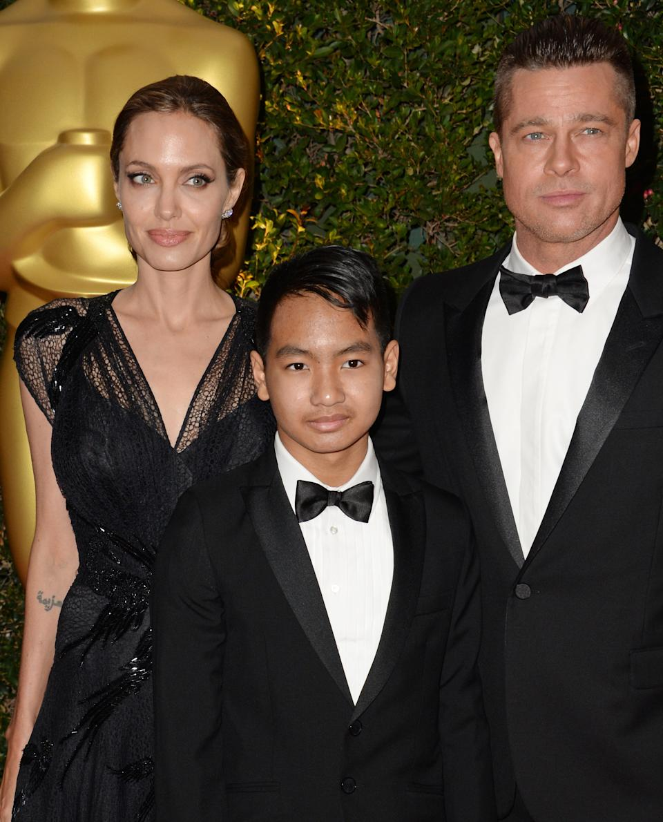 Actress Angelina Jolie, Maddox Jolie-Pitt (C) and actor Brad Pitt arrive for the 2013 Governors Awards, presented by the American Academy of Motion Picture Arts and Sciences (AMPAS), at the Grand Ballroom of the Hollywood and Highland Center in Hollywood, California, November 16, 2013.  AFP PHOTO / Robyn Beck        (Photo credit should read ROBYN BECK/AFP via Getty Images)