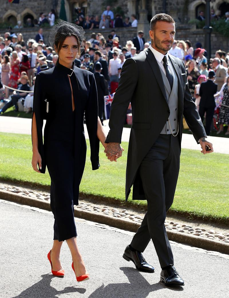 Victoria Beckham and David Beckham hold hands at Meghan Markle and Prince Harry's wedding in 2018