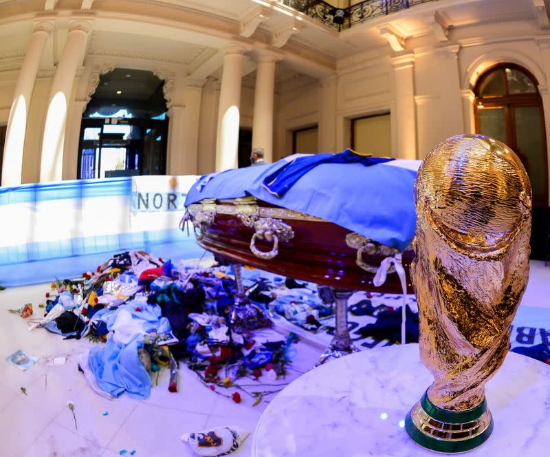A replica of the World Cup Trophy stands next to the casket of soccer legend Diego Maradona at the presidential palace Casa Rosada, in Buenos Aires