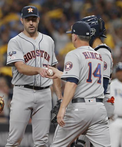 Houston Astros starting pitcher Justin Verlander, left, hands the ball to manager AJ Hinch (14) as he is removed during the fourth inning of Game 4 of the baseball team's American League Division Series against the Tampa Bay Rays, Tuesday, Oct. 8, 2019, in St. Petersburg, Fla. (AP Photo/Scott Audette)