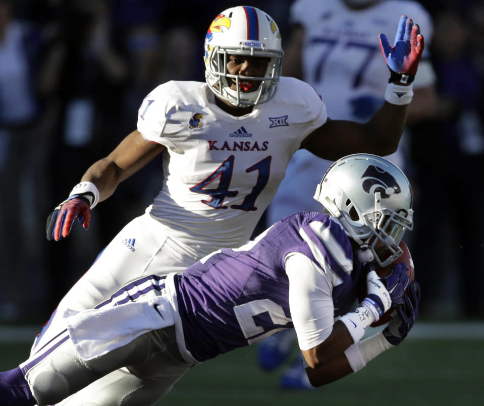 Kansas State defensive back Dante Barnett, right, intercepts a pass intended for Kansas tight end Jimmay Mundine (41) during the first half of an NCAA college football game in Manhattan, Kan., Saturday, Nov. 29, 2014. (AP Photo/Orlin Wagner)