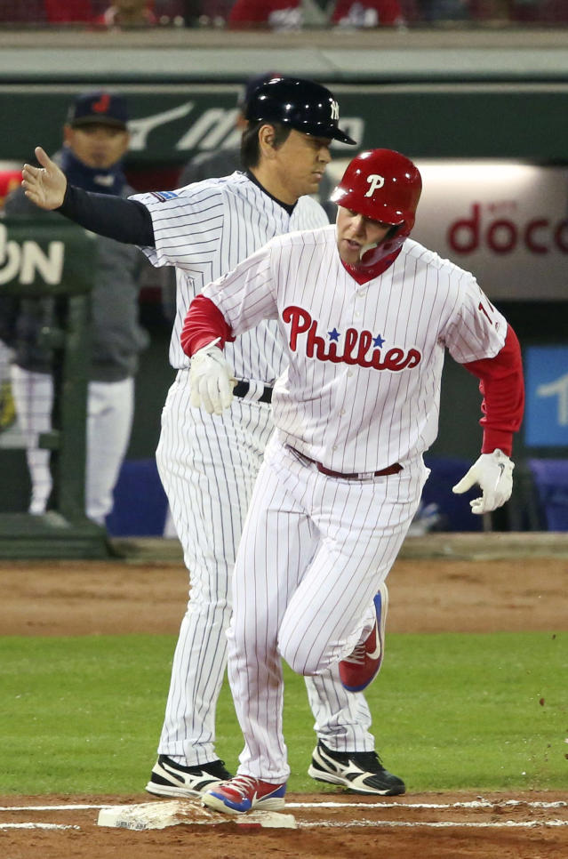 MLB All-Star designated hitter Rhys Hoskins of the Philadelphia Phillies celebrates with first base coach Hideki Matsui after hitting a solo home-run off All Japan starter Daichi Osera in the second inning of Game 4 at their All-Stars Series baseball at Mazda Zoom-Zoom Stadium in Hiroshima, western Japan, Tuesday, Nov. 13, 2018. (Kyodo News via AP)