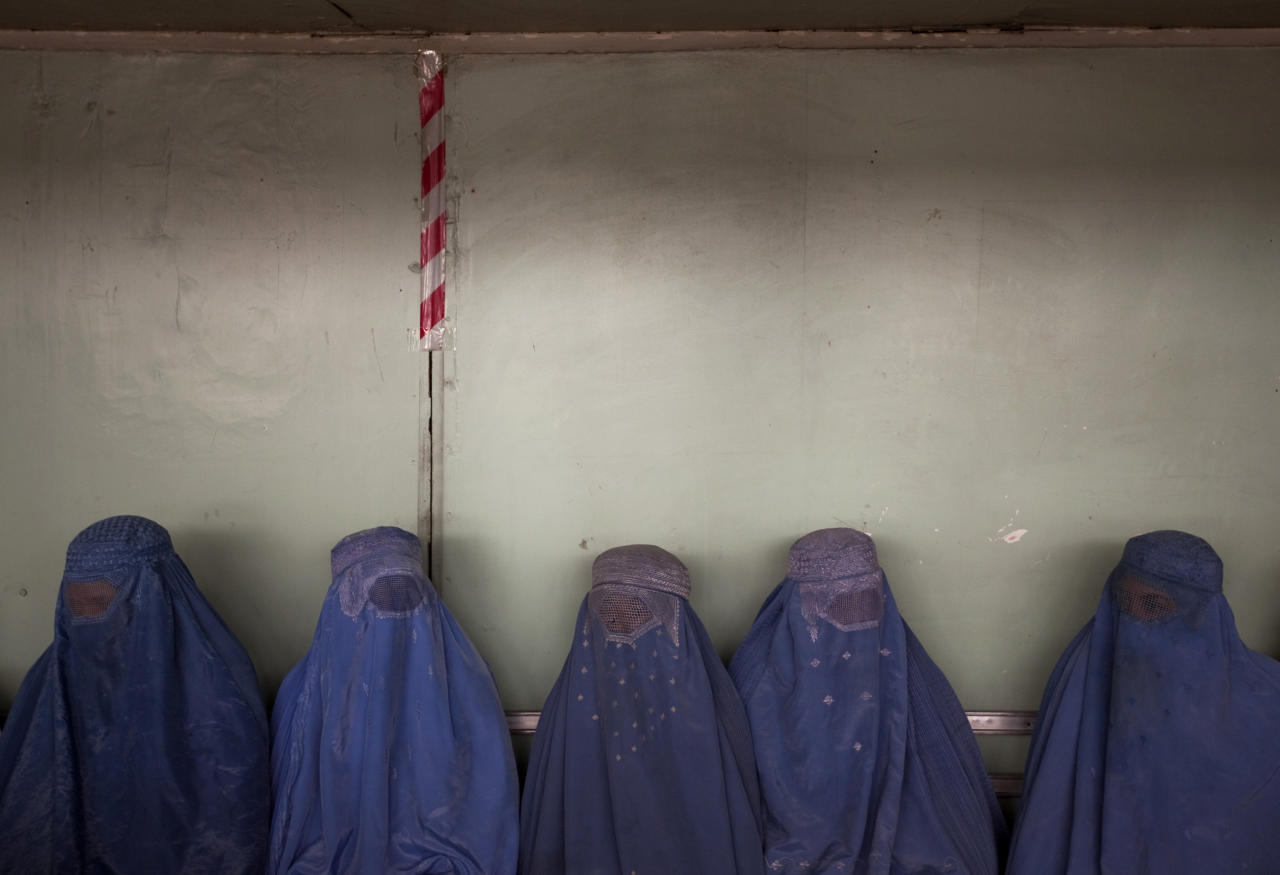 Afghan women wait for their turn to get registered at a voter registration centre in Kabul July 13, 2010. Afghanistan will hold parliamentary elections on September 18.  REUTERS/Ahmad Masood  (AFGHANISTAN - Tags: ELECTIONS POLITICS IMAGES OF THE DAY)