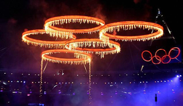 London: The Olympic rings are illuminated with pyrotechnics as they are raised above the stadium during the Opening Ceremony at the 2012 Summer Olympics in London on Friday. PTI Photo by Manvender Vashist(PTI7_28_2012_000024B)