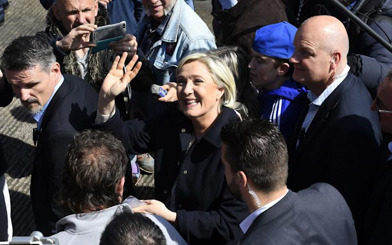 Marine Le Pen greets people during her visit to the harbour in Erquy, western France on March 31 - Credit: DAMIEN MEYER/AFP