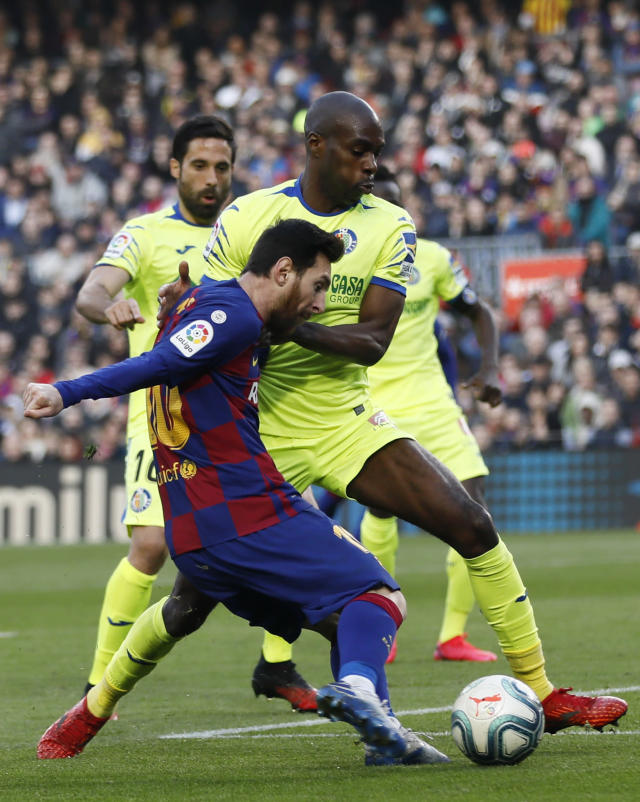 Barcelona's Lionel Messi, front, is blocked by Getafe's Allan Nyom during a Spanish La Liga soccer match between Barcelona and Getafe at the Camp Nou stadium in Barcelona, Spain, Saturday Feb. 15, 2020. (AP Photo/G.Garin)