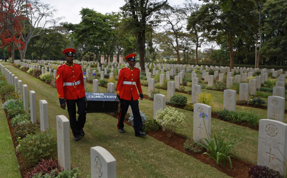 "FILE - In this Sunday, Nov. 13, 2016 file photo, two members of Kenya's Military Police walk past graves as they leave after attending a Remembrance Sunday event, to honor the contribution of those British and Commonwealth military who died in the two World Wars and later conflicts, at the Nairobi War Cemetery in Kenya. The Commonwealth War Graves Commission has apologized after an investigation found that at least 161,000 mostly Africans and Indians who died fighting for the British Empire during World War I weren't properly honored due to ""pervasive racism"", according to findings released Thursday, April 22, 2021. (AP Photo/Ben Curtis, File)"