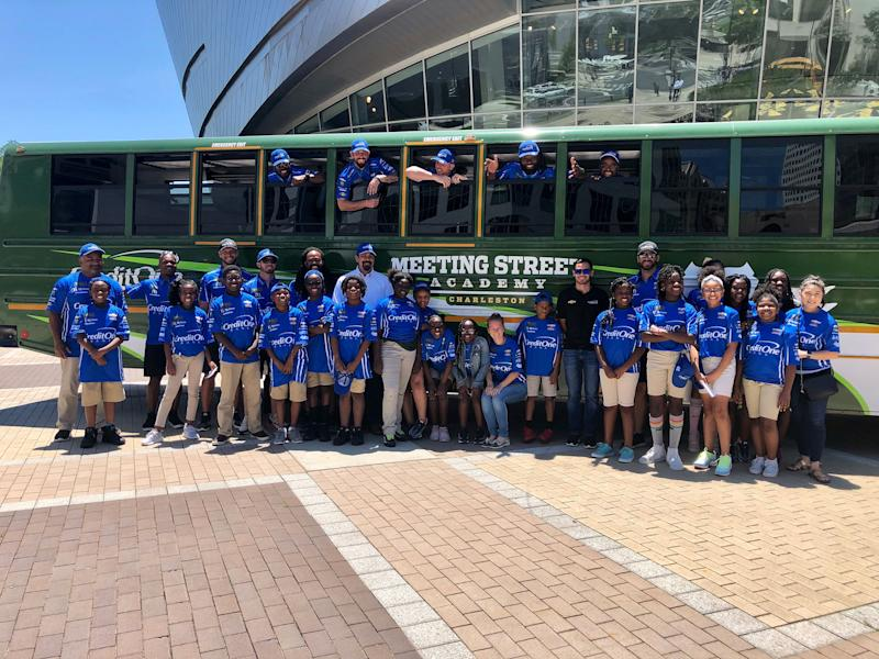 Kyle Larson poses with students from Meeting Street Academy next to the bus donated to the school by Credit One Bank and the NASCAR Foundation