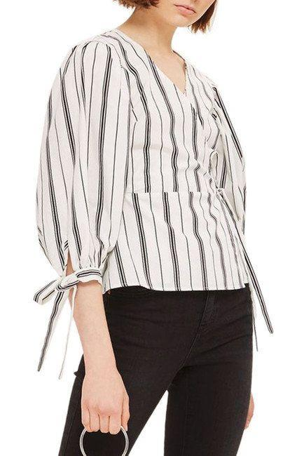 """Get it <a href=""""https://www.nordstromrack.com/shop/product/2273515/topshop-balloon-sleeve-stripe-wrap-top?color=WHITE%20MULTI"""" target=""""_blank"""">here</a>.&nbsp;"""