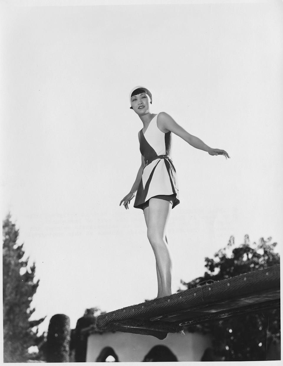 Anna May Wong stands on a roof wearing a black and white ensemble, undated.