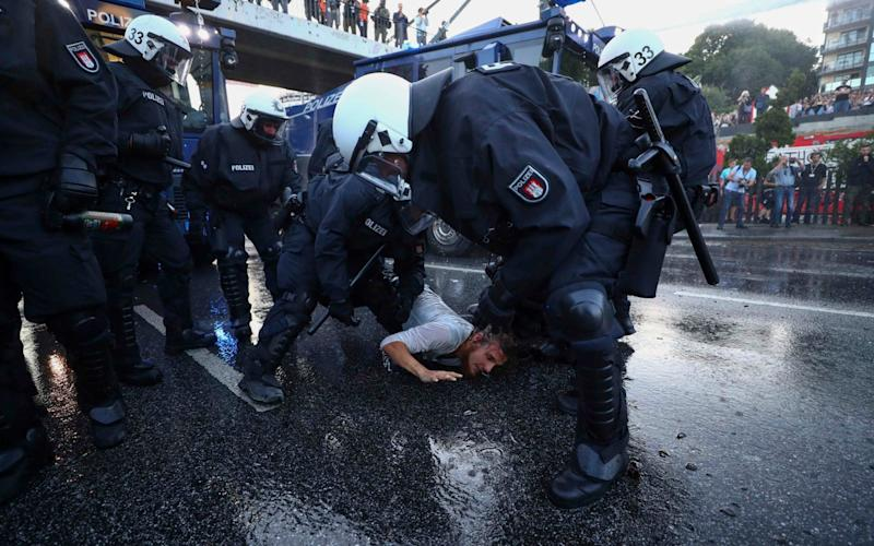 German riot police detain a protester during the demonstrations during the G20 summit in Hamburg - Credit: Reuters