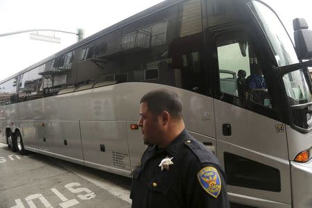 A San Francisco police officer stands in front of a Google commuter bus after clearing demonstrators blocking its path in the Mission District in San Francisco