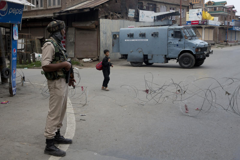 In this Tuesday, Aug. 6, 2019 photo, a Kashmiri boy walks past an Indian Paramilitary soldier after buying fresh bread during curfew in Srinagar, Indian controlled Kashmir, Wednesday, Aug. 7, 2019. Authorities in Hindu-majority India clamped a complete shutdown on Kashmir as they scrapped the Muslim-majority state's special status, including exclusive hereditary rights and a separate constitution, and divided it into two territories. (AP Photo/Dar Yasin)