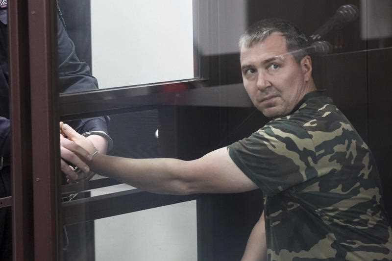 Alexander Popov. who was arrested on suspicion of murder. sits behind the glass in a courtroom in the city of Gorodets.