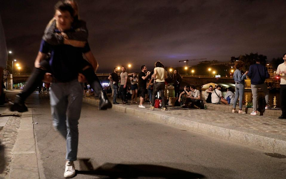 People stand on the banks of the Seine River past the 11pm Covid-19 curfew, early on June 12, 2021, after people gathered nearby at Les Invalides for an unauthorized outdoor party. - Geoffroy Van Der Hasselt/AFP