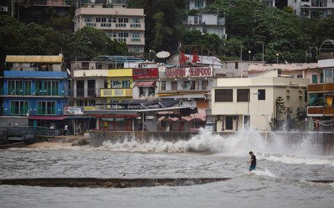 A man walks out on a low-lying wharf while large waves caused by Typhoon Hato break along the waterfront in Hong Kong's Lamma Island - Credit: AFP