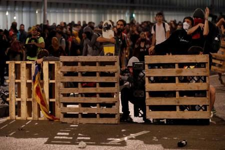 Protesters build a barricade during a demonstration at the airport, after a verdict in a trial over a banned independence referendum, in Barcelona