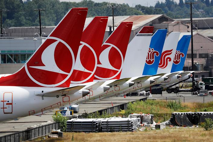 """The tails of several of the dozens of grounded Boeing 737 MAX airplanes line the edge of a parking area adjacent to Boeing Field Thursday, June 27, 2019, in Seattle. A new software problem has been found in the troubled Boeing 737 Max that could push the plane's nose down automatically, and fixing the flaw is almost certain to further delay the plane's return to flying after two deadly crashes. Boeing said Wednesday, June 26, 2019, that the FAA """"identified an additional requirement"""" for software changes that the aircraft manufacturer has been working on for eight months, since shortly after the first crash. (AP Photo/Elaine Thompson)"""