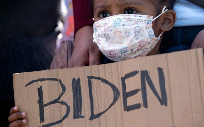 Dareli Matamoros, a girl from Honduras, holds a sign asking President Joe Biden to let her in at a border crossing in Tijuana - GUILLERMO ARIAS/AFP