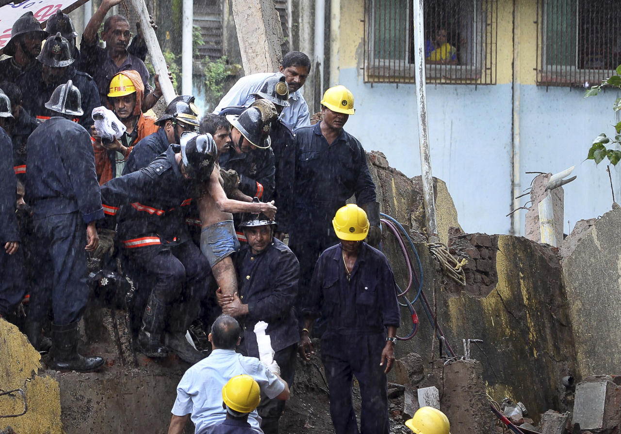 Indian Fire officials rescue an injured resident from debris of a collapse building in Mumbai, India, Friday, Sept. 27, 2013. The multi-story residential building collapsed in India's financial capital of Mumbai early Friday, killing at least three people and sending rescuers racing to reach dozens of people feared trapped in the rubble. (AP Photo/Rajanish Kakade)