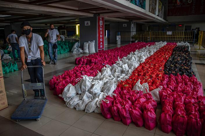 Volunteers pack relief goods for residents running out of food and supplies as they undergo home quarantine on March 20, 2020 in Quezon city, Metro Manila, Philippines.