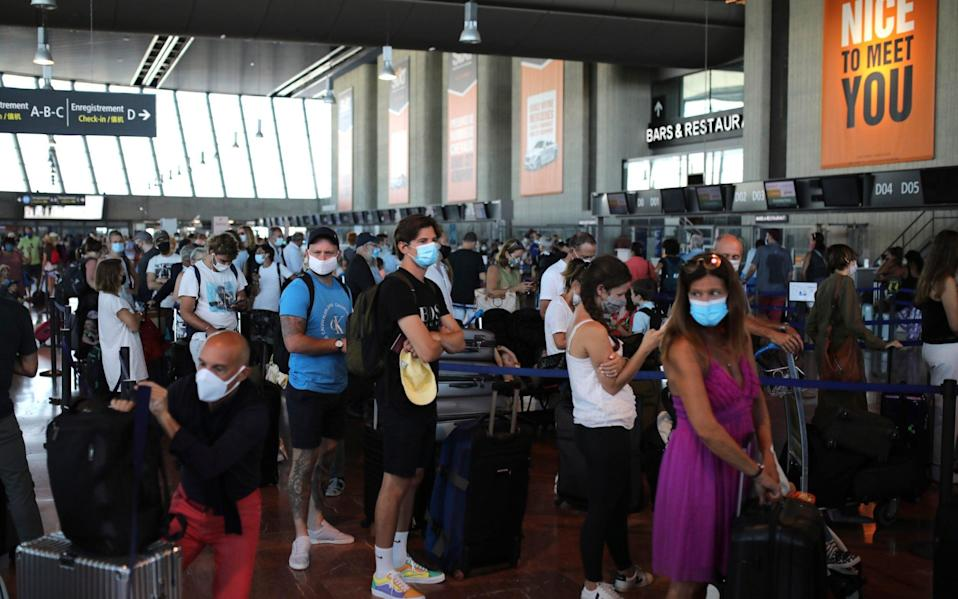 People queue in line to check-in for a British Airways flight to Heathrow airport from Nice airport - AP Photo/Daniel Cole