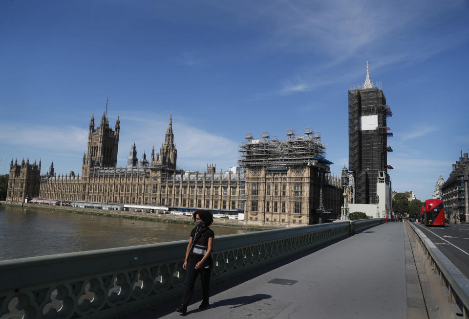 A pedestrian walks over Westminster Bridge alongside Parliament in London, Tuesday, June 2, 2020. The British government has decided to scrap a remote-voting system used during the coronavirus pandemic, and has summoned lawmakers back to parliament on Tuesday, but many aren't happy with the arrangements. (AP Photo/Frank Augstein)