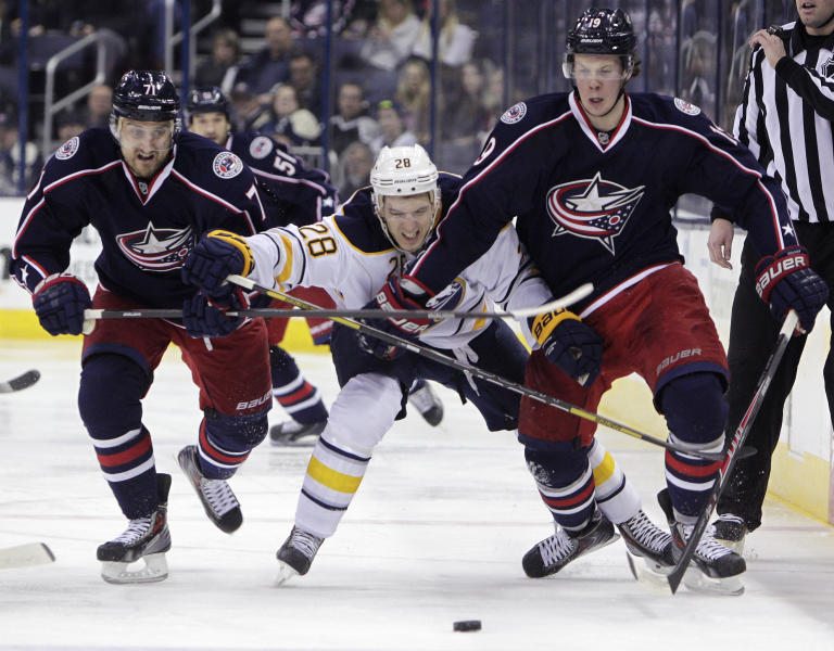 Columbus Blue Jackets' Nick Foligno, left, Ryan Johansen, right, and Buffalo Sabres' Zemgus Girgensons, of Latvia, chase a loose puck during the second period of an NHL hockey game, Saturday, Jan. 25, 2014, in Columbus, Ohio. (AP Photo/Jay LaPrete)