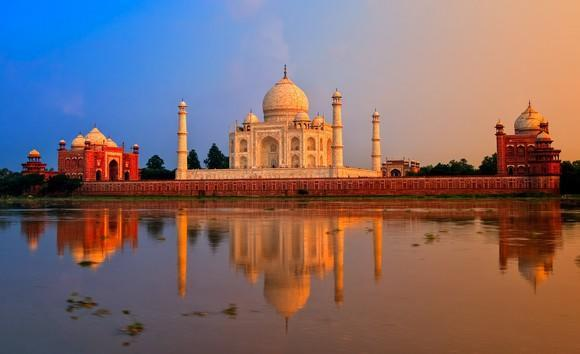 Taj Mahal with two other buildings and the Yamuna River in the foreground.