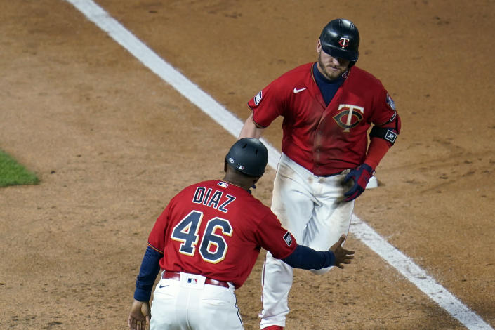 Minnesota Twins' Josh Donaldson, right, is congratulated by third base coach Tony Diaz on his two-run home run off Chicago White Sox pitcher Dallas Keuchel in the sixth inning of a baseball game, Monday, May 17, 2021, in Minneapolis. (AP Photo/Jim Mone)