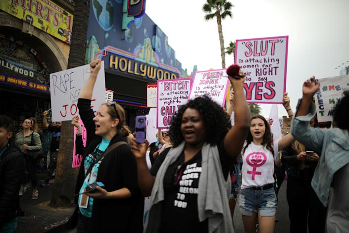 Protesters hold signs as they march through Hollywood.
