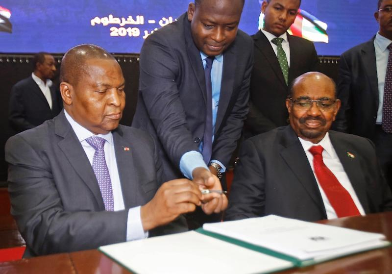 Central African Republic President Faustin-Archange Touadera, left, inks the peace deal next to Sudanese President Omar al-Bashir in Khartoum on February 5 (AFP Photo/ASHRAF SHAZLY)