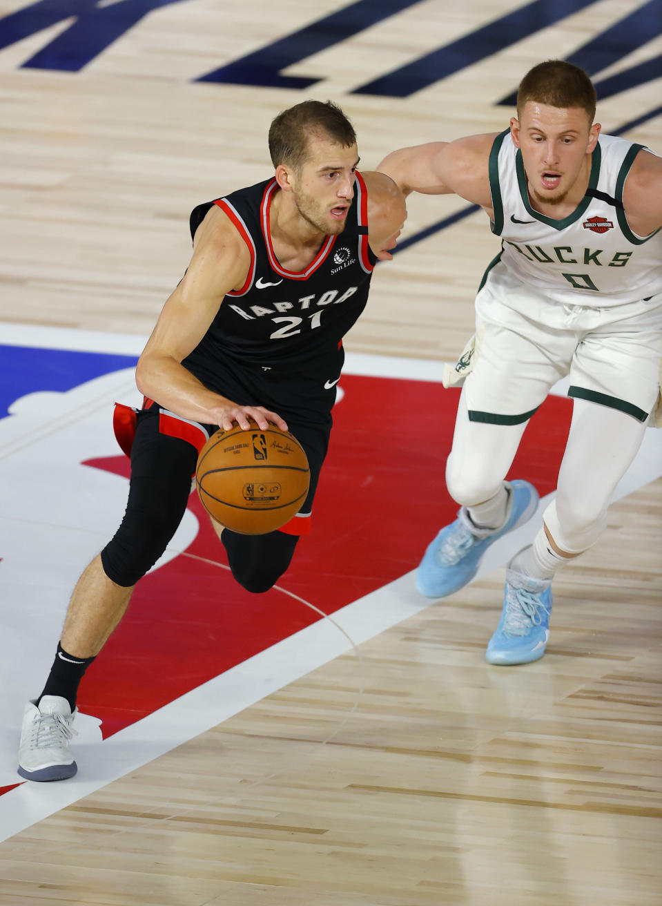 Toronto Raptors' Matt Thomas moves the ball as Milwaukee Bucks' Donte DiVincenzo defends during the fourth quarter of an NBA basketball game Monday, Aug. 10, 2020, in Lake Buena Vista, Fla. (Mike Ehrmann/Pool Photo via AP)