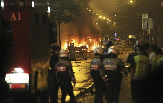 Riot policemen watch burning vehicles during a riot in Singapore's Little India district, late December 8, 2013. A crowd set fire to vehicles and clashed with police in the Indian district of Singapore late on Sunday, in a rare outbreak of rioting in the city state. Television footage showed a crowd of people smashing the windscreen of a bus, and at least three police cars being flipped over. The Singapore Police Force said the riot started after a fatal traffic accident in the Little India area. REUTERS/Dennis Thong/Lianhe Zaobao (SINGAPORE - Tags: CIVIL UNREST TPX IMAGES OF THE DAY) ATTENTION EDITORS - THIS IMAGE HAS BEEN SUPPLIED BY A THIRD PARTY. IT IS DISTRIBUTED, EXACTLY AS RECEIVED BY REUTERS, AS A SERVICE TO CLIENTS. NO SALES. NO ARCHIVES. FOR EDITORIAL USE ONLY. NOT FOR SALE FOR MARKETING OR ADVERTISING CAMPAIGNS. SINGAPORE OUT. NO COMMERCIAL OR EDITORIAL SALES IN SINGAPORE