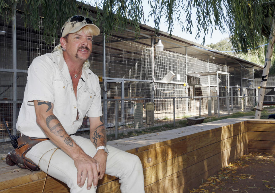"""FILE - In this Aug. 28, 2013, file photo, Joseph Maldonado answers a question during an interview at the zoo he runs in Wynnewood, Okla. Federal prosecutors on Friday, Sept. 7, 2018, announced that the zookeeper, also known as """"Joe Exotic,"""" and candidate for governor earlier this year, has been charged in a murder-for-hire scheme alleging he tried to hire someone to kill a Florida woman. Prosecutors allege Maldonado-Passage tried to hire two separate people to kill the woman, who wasn't harmed. Maldonado-Passage finished third in a three-way Libertarian primary in June. (AP Photo/Sue Ogrocki, File)"""
