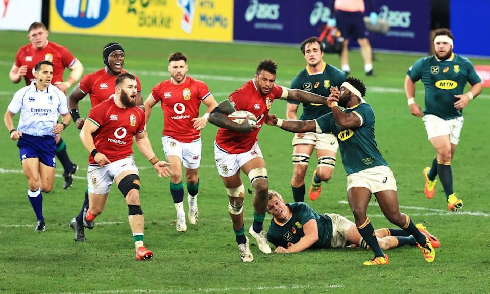 Courtney Lawes hands off South Africa's Siya Kolisi during a colossal performance.