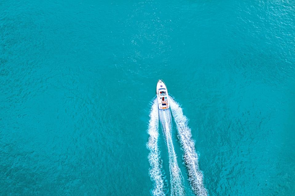 Speed boat on  azure sea in turquoise blue water -  birdseye aerial view of boat