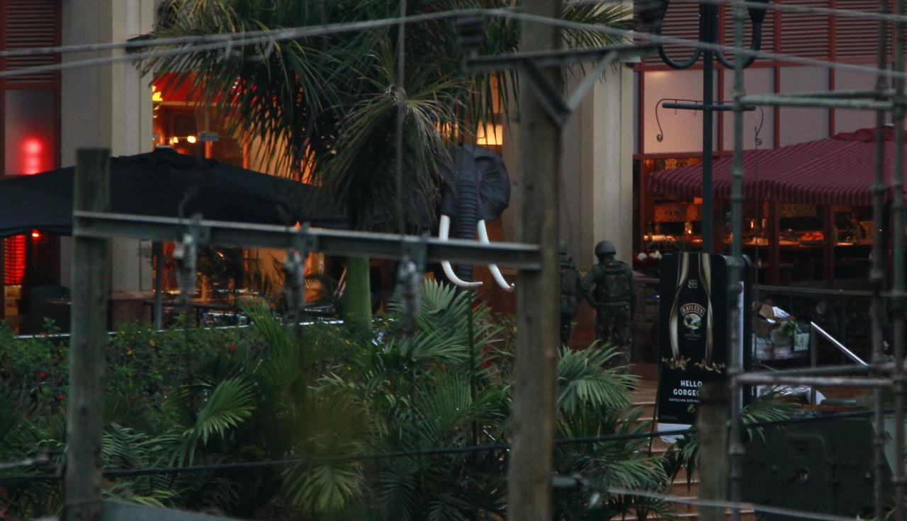 Soldiers from the Kenya Defence Forces (KDF) are seen entering the Westgate Shopping Centre in the capital Nairobi, September 23, 2013. Heavy and sustained gunfire was heard from the Kenyan shopping mall where at least 68 people were killed in an attack by the Somali al Shabaab group, suggesting a possible assault by Kenyan security forces, a Reuters witness at the scene said. REUTERS/Thomas Mukoya (KENYA - Tags: SOCIETY CIVIL UNREST CRIME LAW)