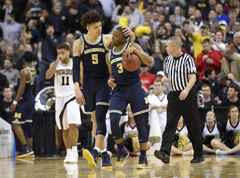 Michigan forward D.J. Wilson (5) and guard Xavier Simpson (3) react during the overtime of an NCAA college basketball game in the Big Ten tournament as Purdue guard P.J. Thompson (11) is seen at back, Friday, March 10, 2017, in Washington. Michigan won 74-70 in overtime. (AP Photo/Nick Wass)