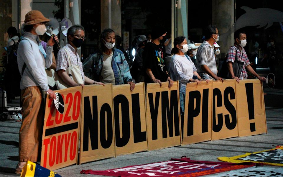 Anti-Olympic protestors demonstrate in front of the Harumi Island Triton Square, where the office of the Tokyo 2020 Organising Committee is located, in Tokyo on 30 July 2021 - Kantaro Komiya/AP
