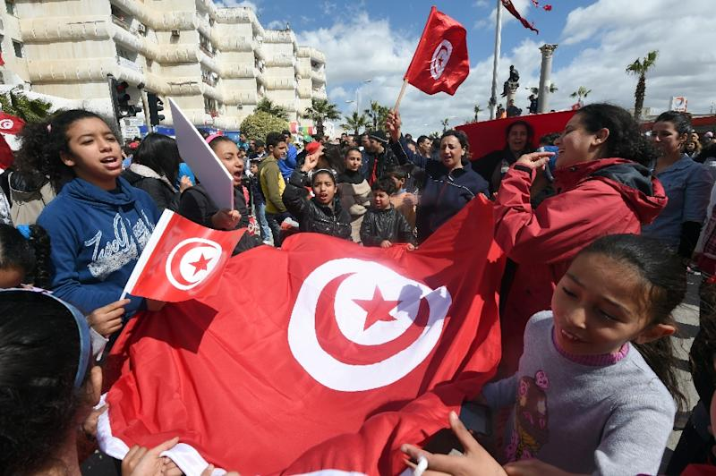 Tunisians wave their national flag during a march against extremism outside the Bardo Museum in Tunis on March 29, 2015 (AFP Photo/Fethi Belaid)